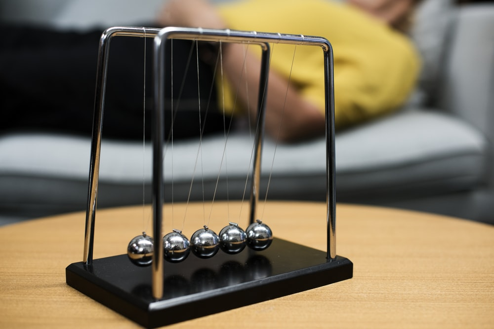 selective focus photography of gray Newton's Cradle on brown wooden table
