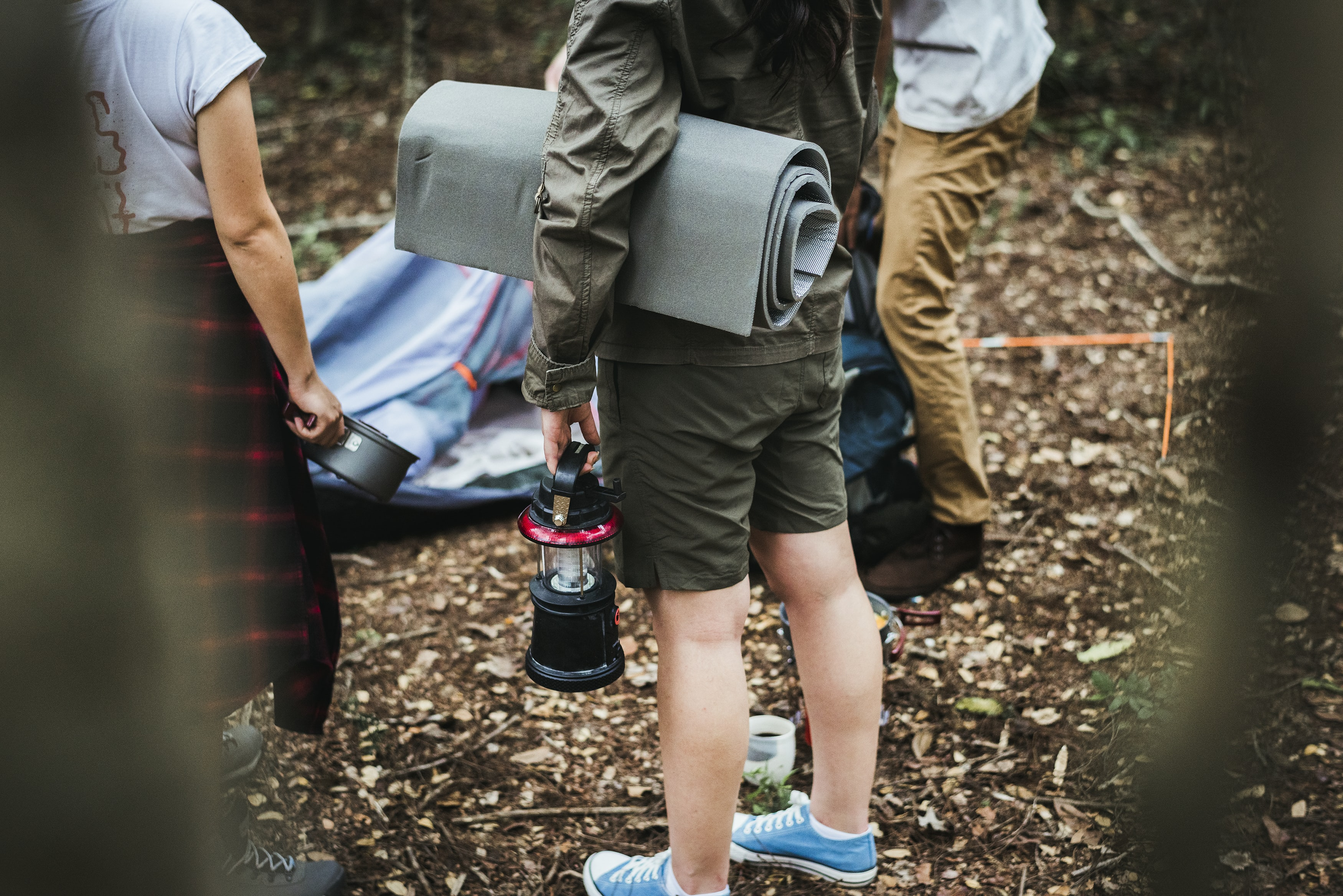 person holding black and red LED camping lamp