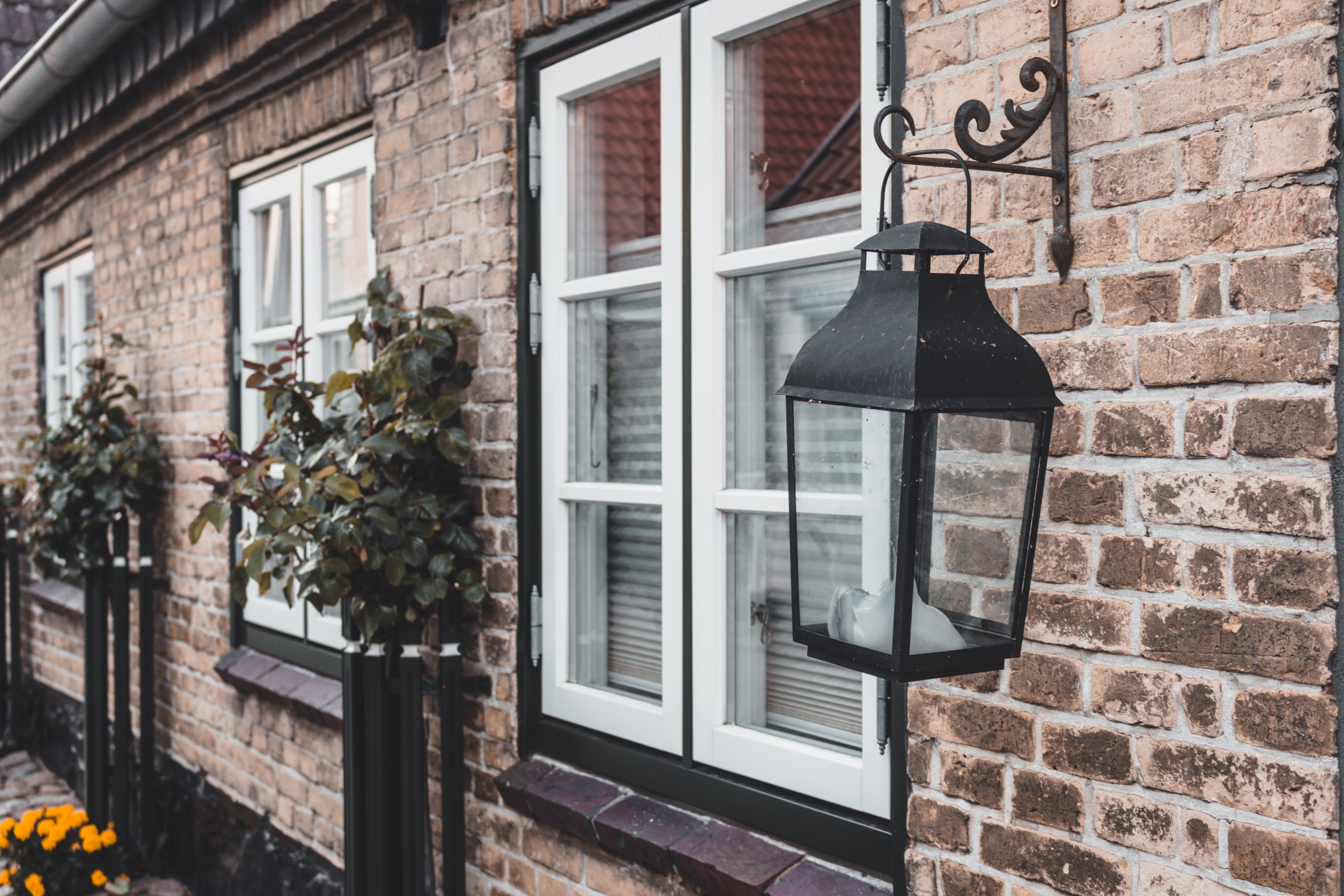 black outdoor sconce light on brown brick wall