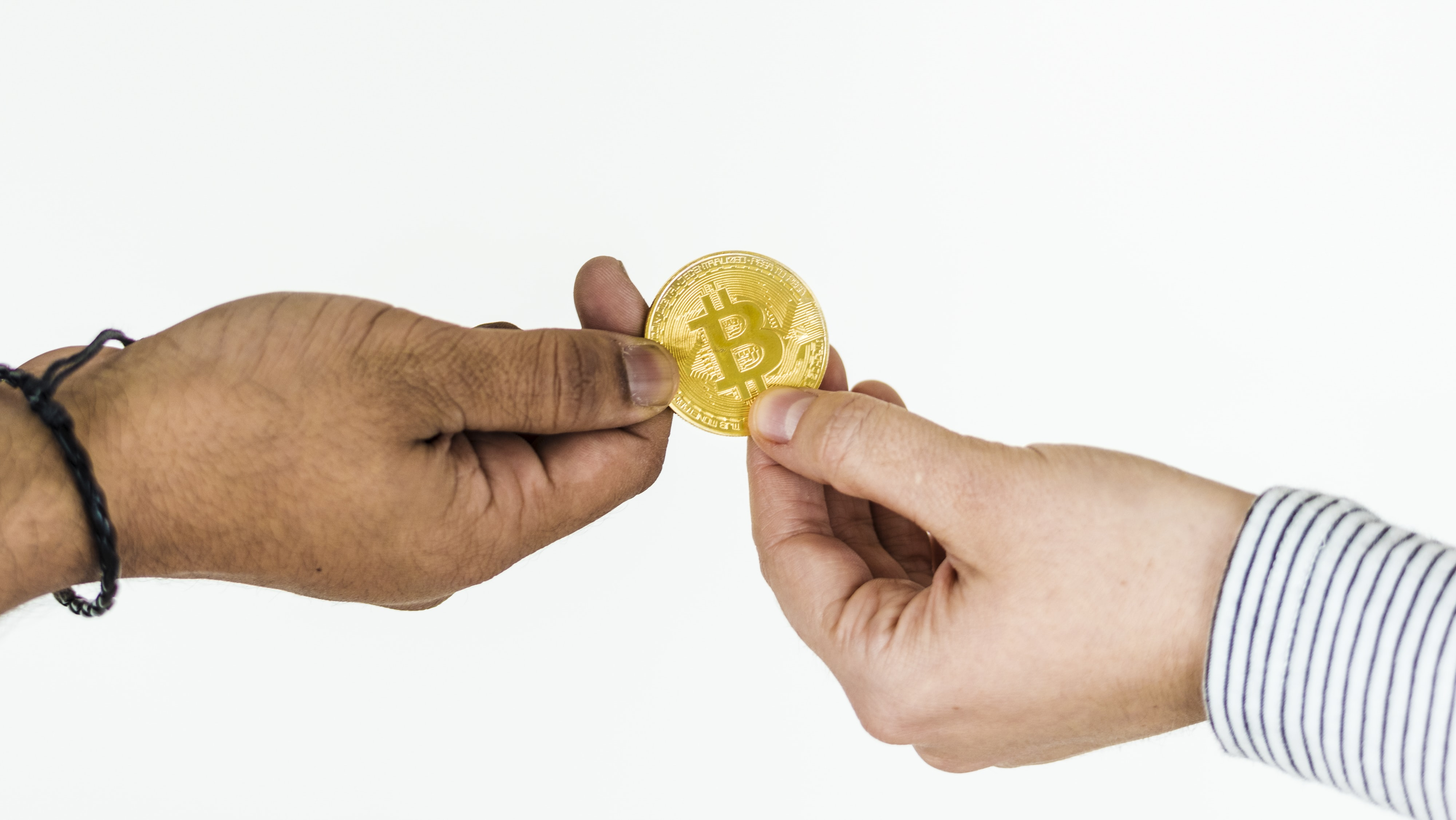 two persons holding gold-colored Bitcoin