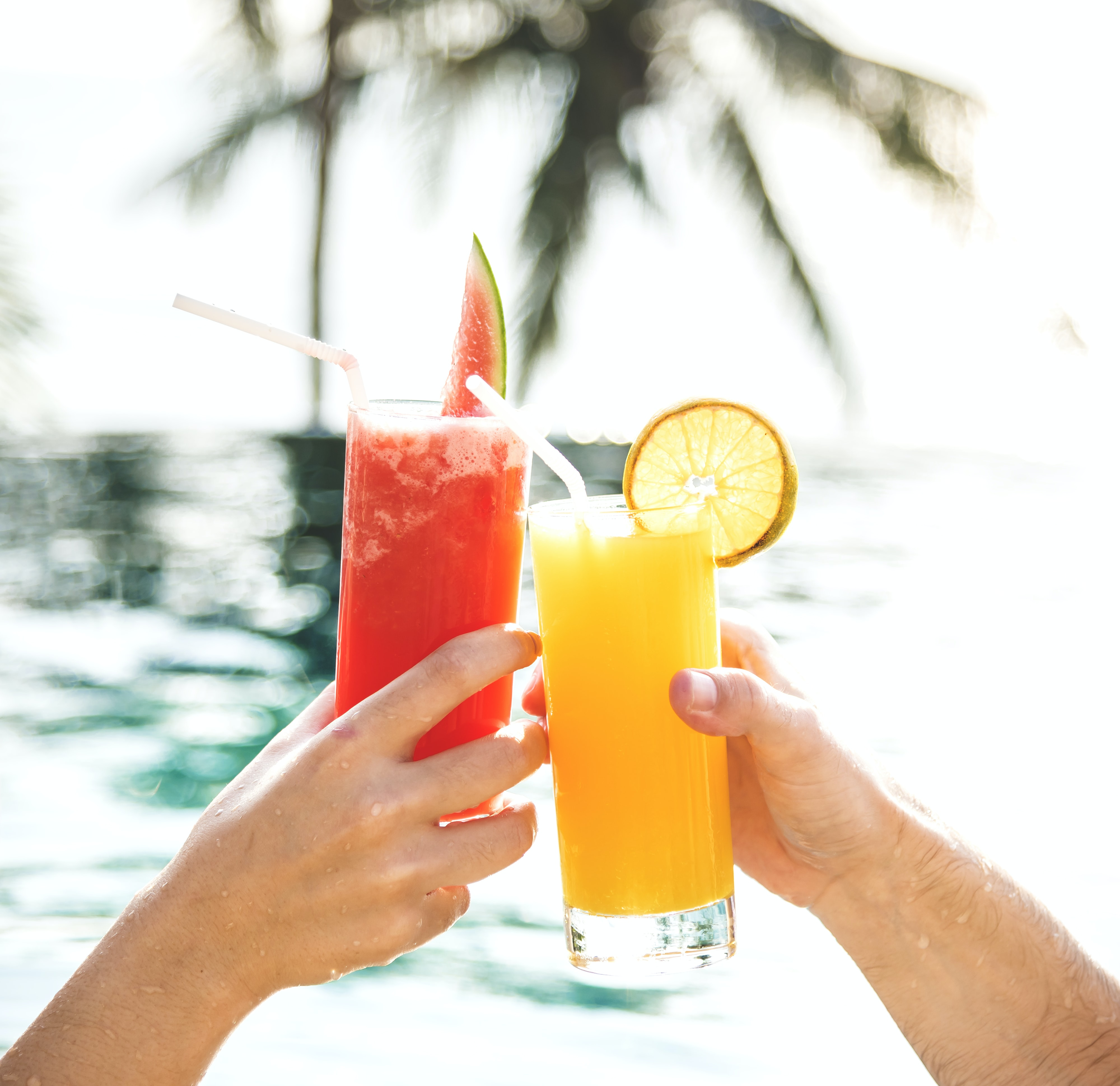 people toasting clear drinking glass with lemon and watermelon juices