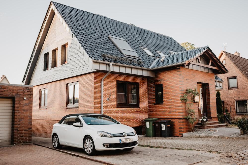white Volkswagen Jetta parked beside house