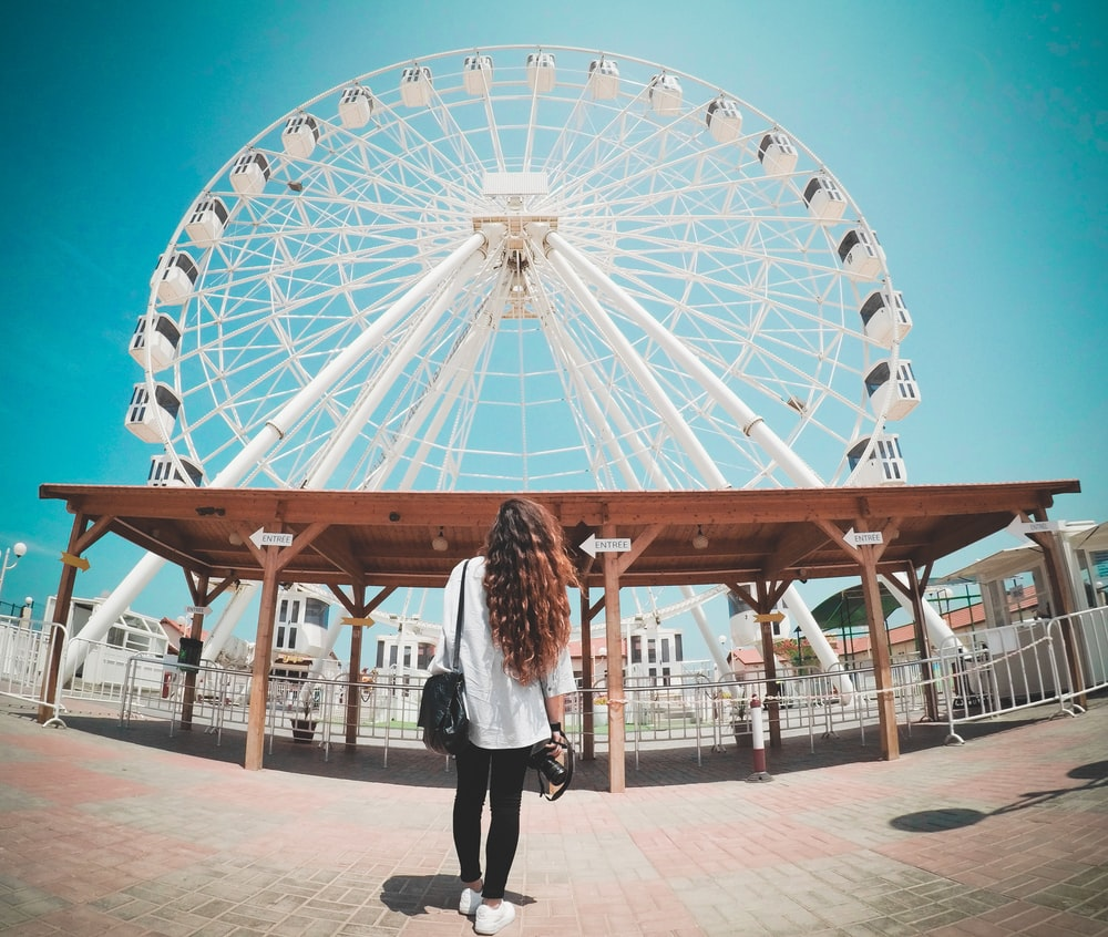 long-haired woman stares at white Ferris Wheel inside the amusement park