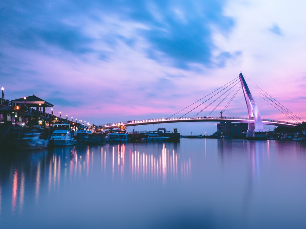 gray bridge with lights near boat at daytime