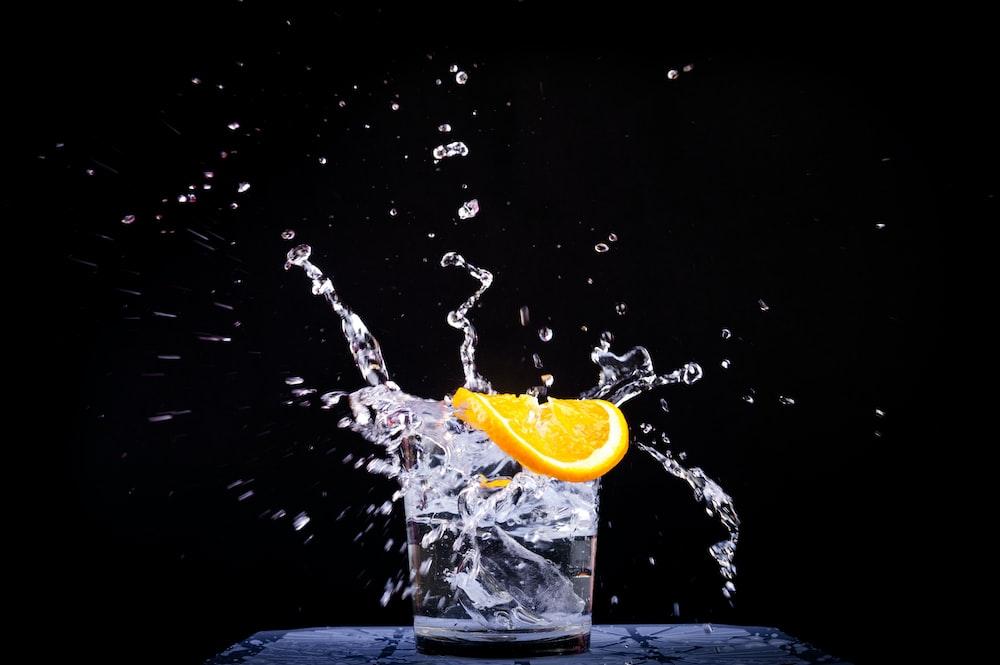 splash of water in drinking glass with sliced lemon