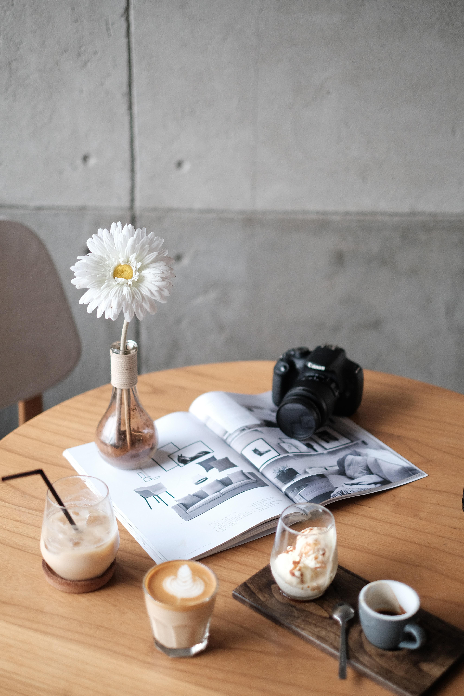 black Canon DSLR camera on white book beside white flower