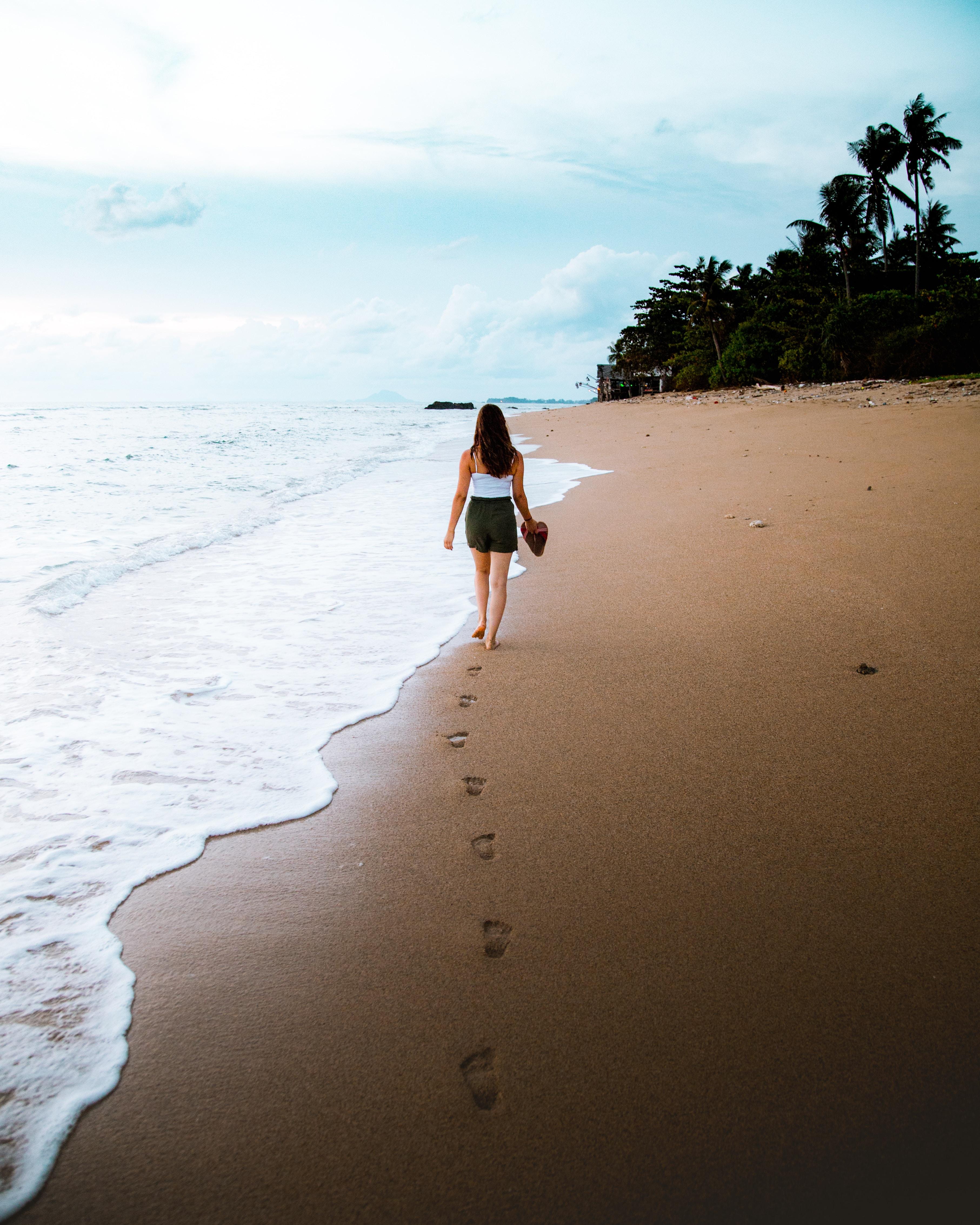 woman walking in front of beach