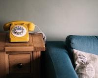 photo of yellow rotary telephone near blue sofa
