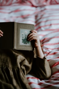 person laying on bed while reading a book