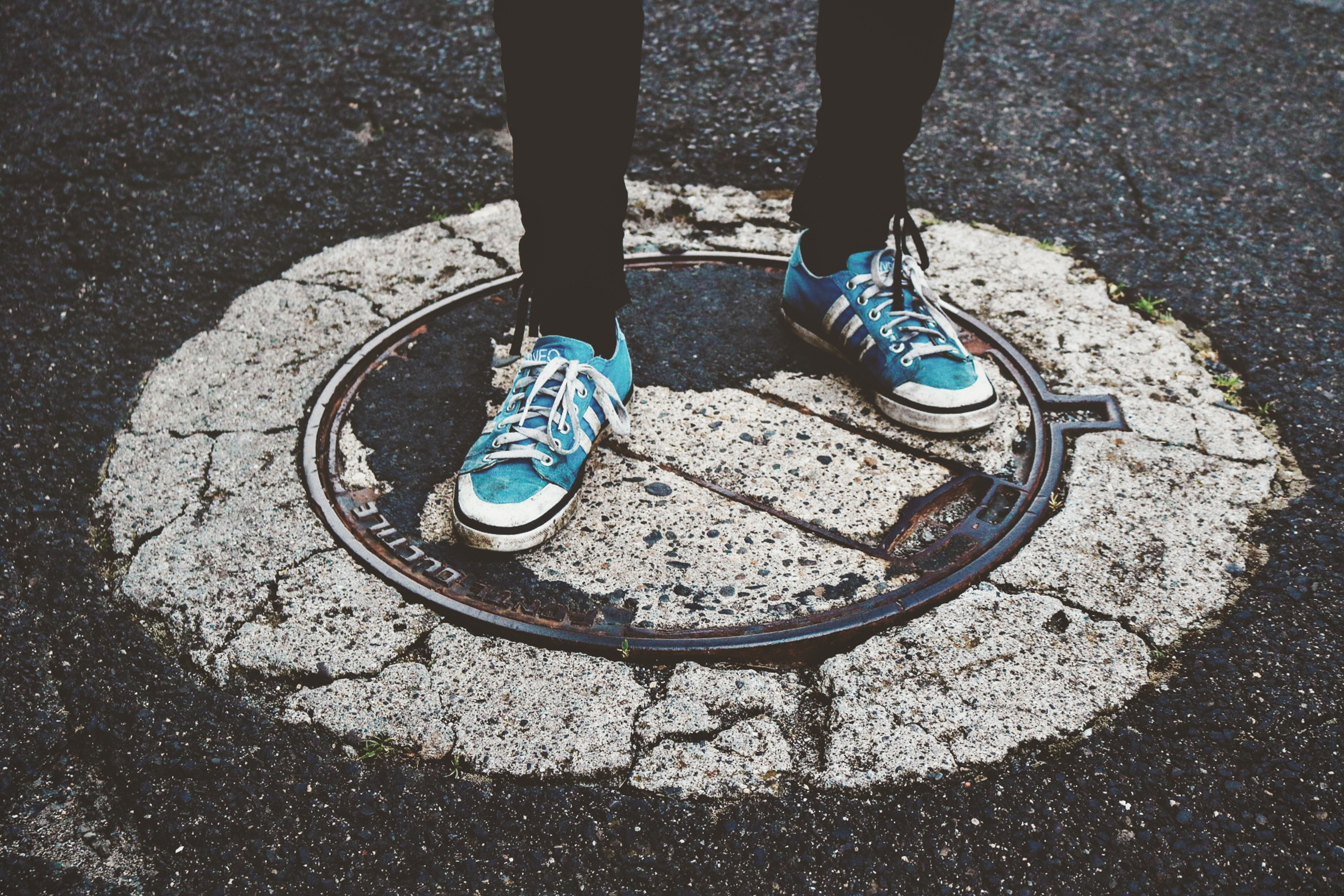 person wearing blue-and-white sneakers standing on pavement at daytimew