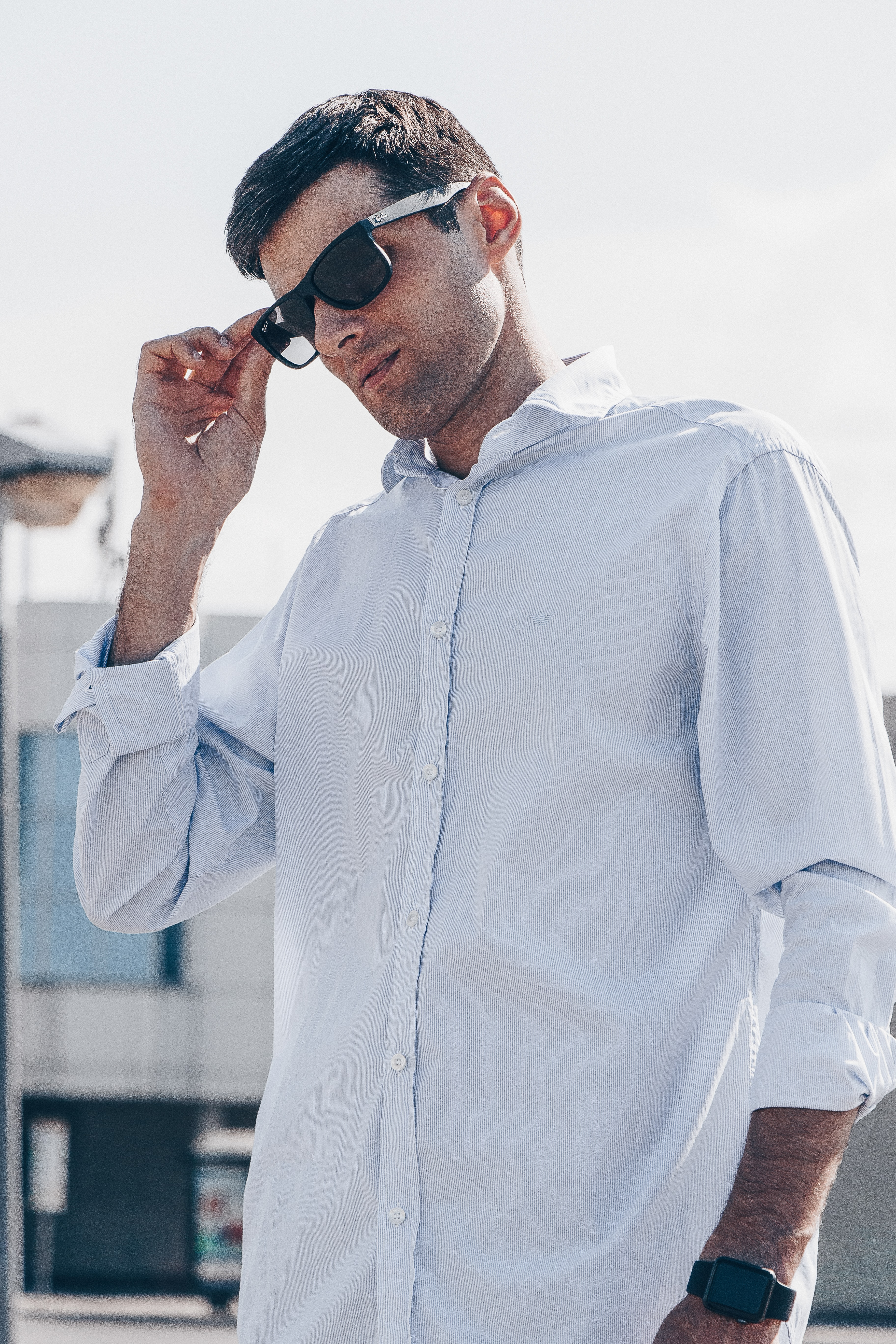 man wearing white dress shirt holding sunglasses
