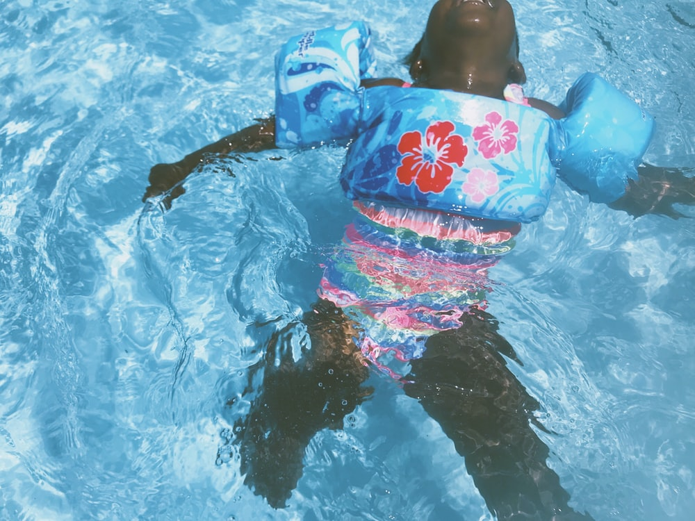 toddler wearing blue floral pool float on swimming pool