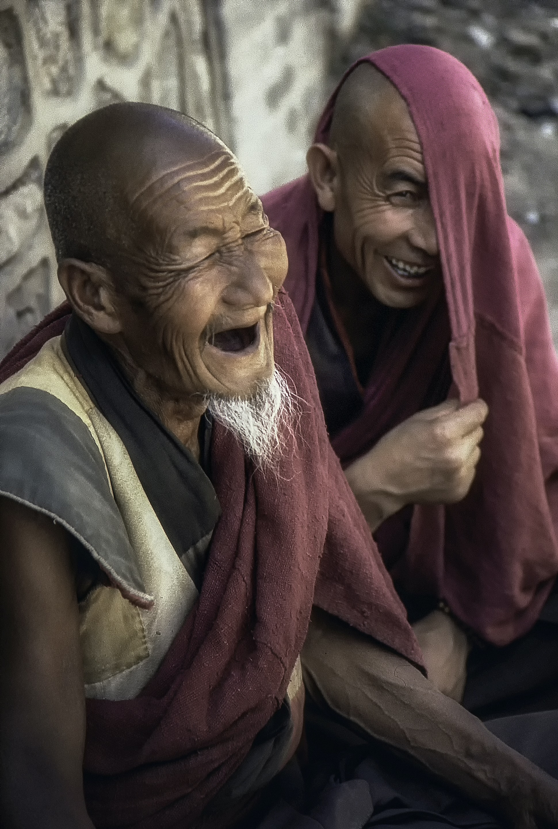 two laughing men near gray wall during daytime