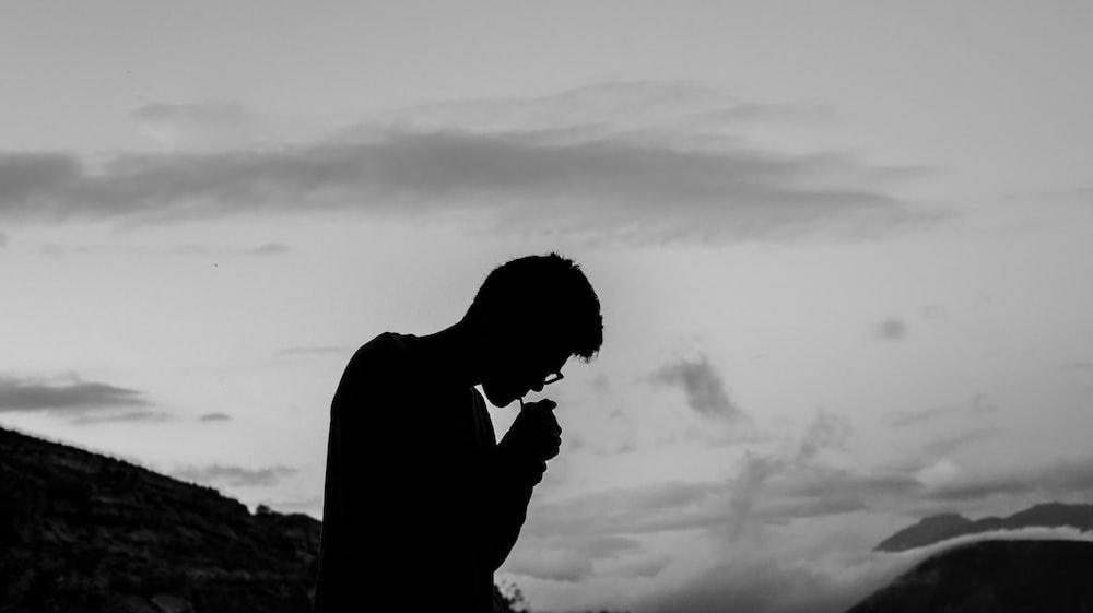 silhouette photo of man smoking outdoors