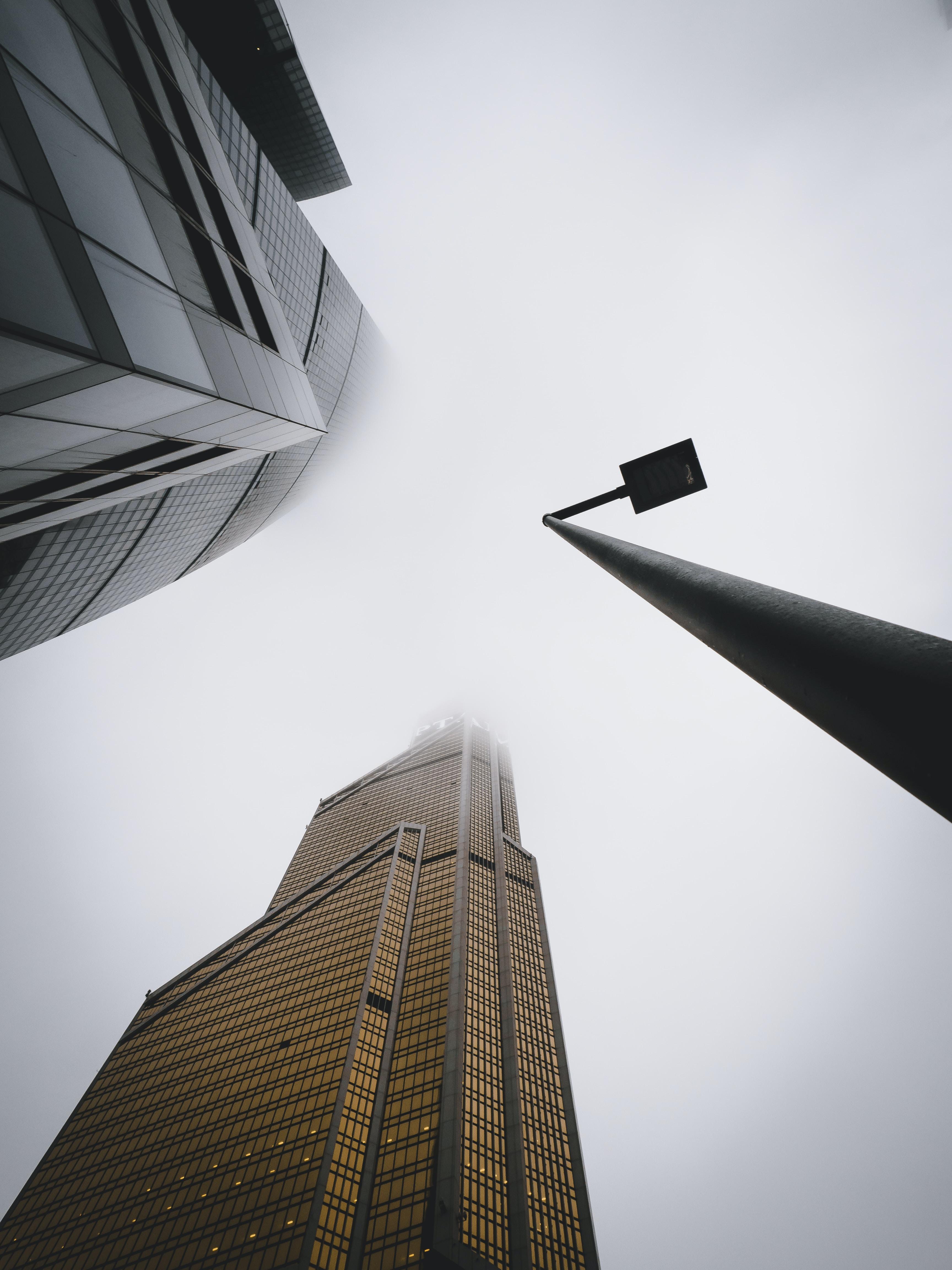 street light near city buildings under gray sky during daytime