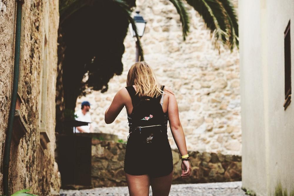 woman walking on alley while facing backwards