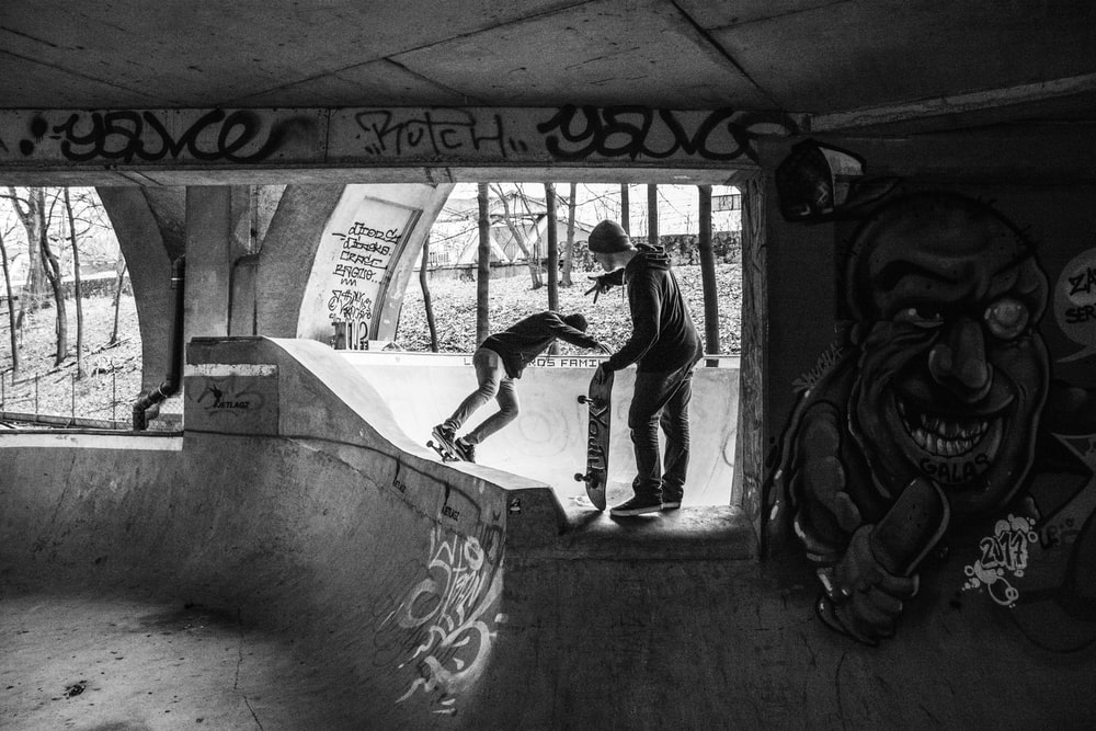 grayscale of two people on skateboard bowl