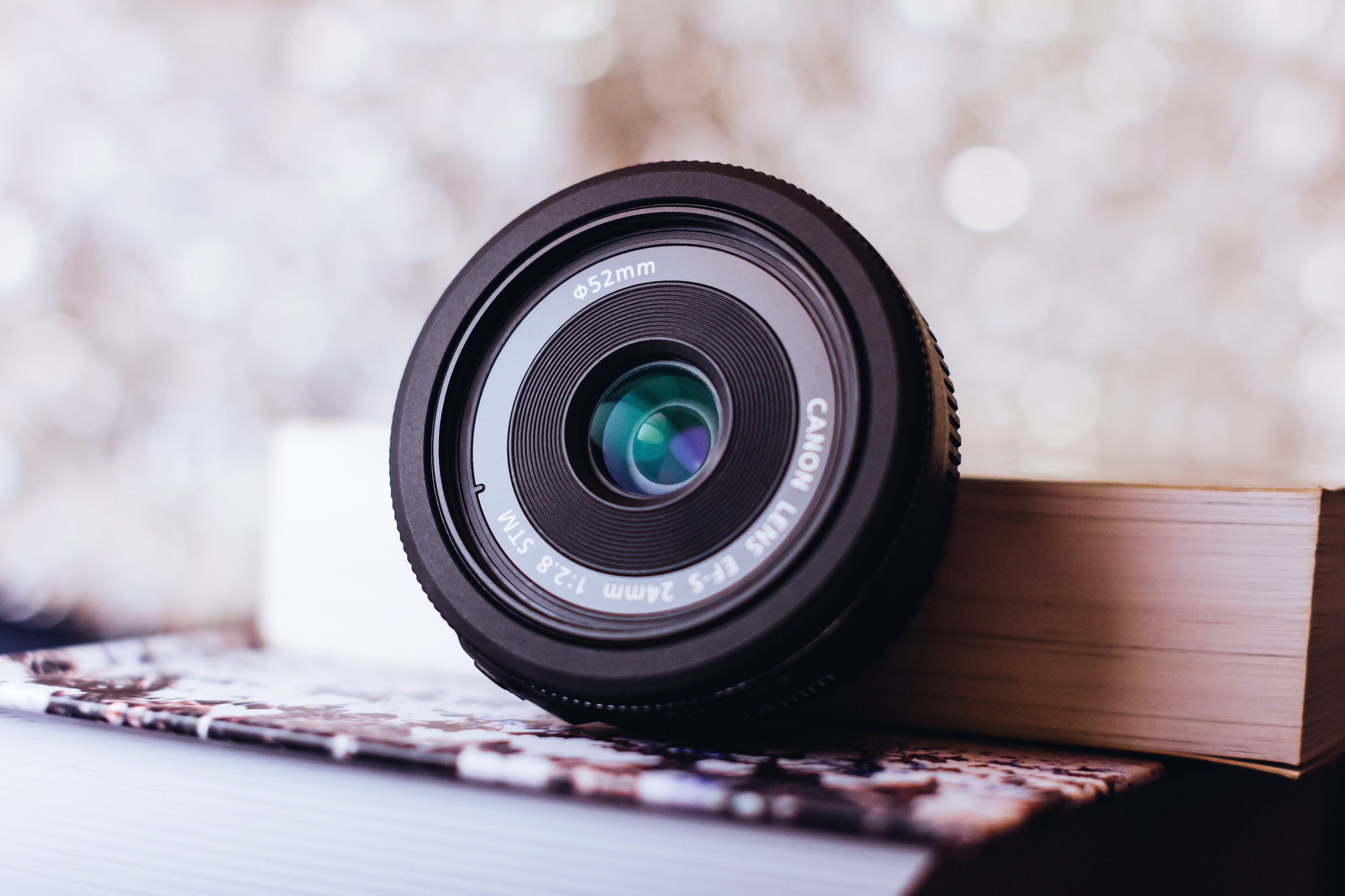 black Canon camera lens leaning on white book