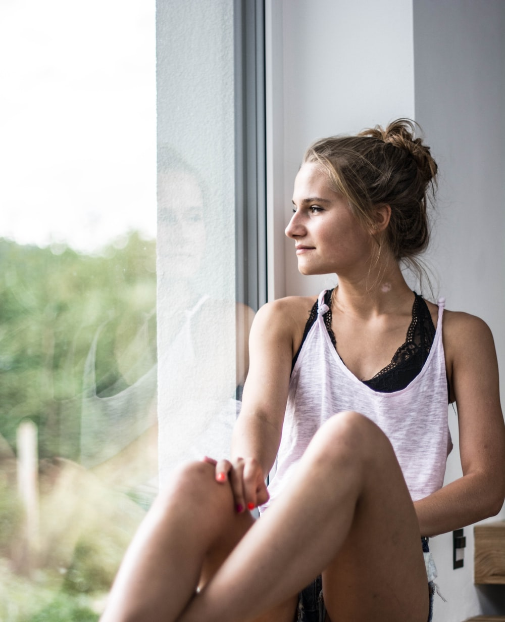woman sitting beside window overlooking trees