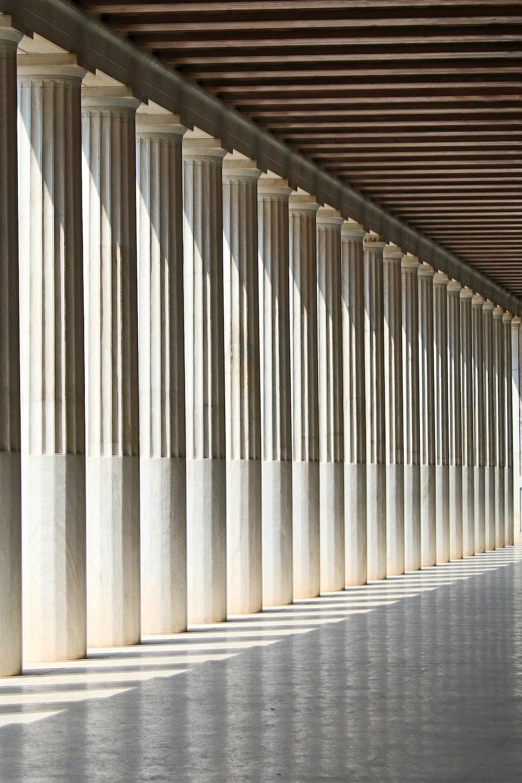 inline white concrete pillars with empty hallway