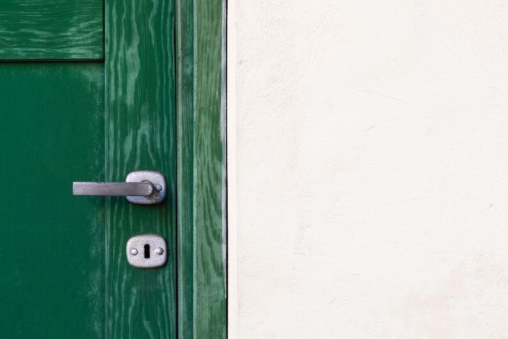 green wooden door beside white wall