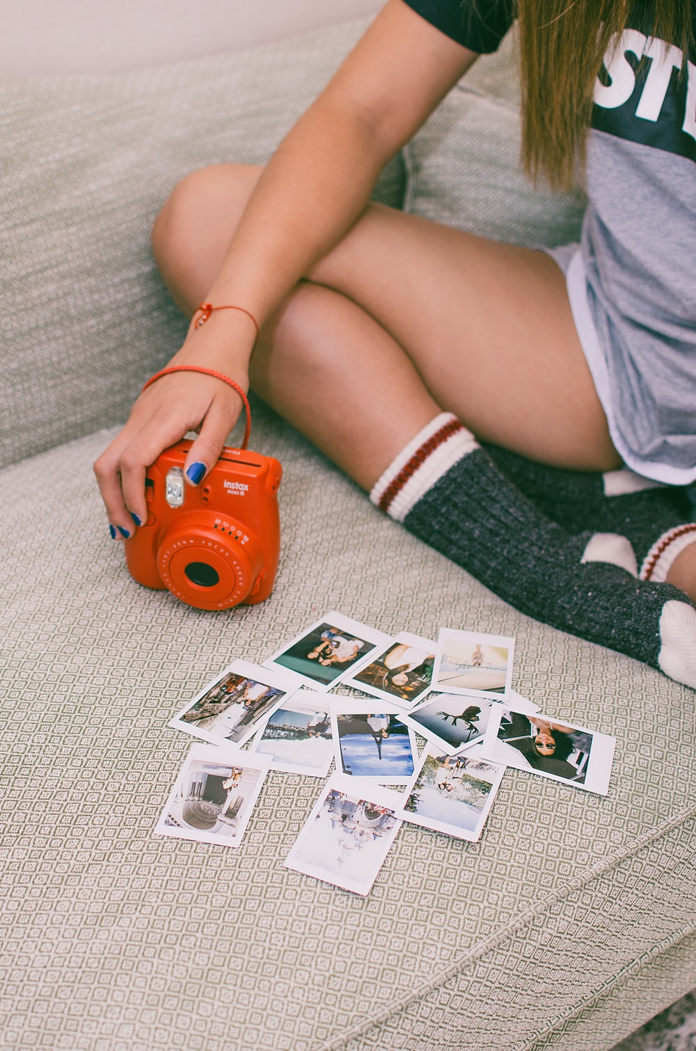 person sitting on couch holding red instant camera