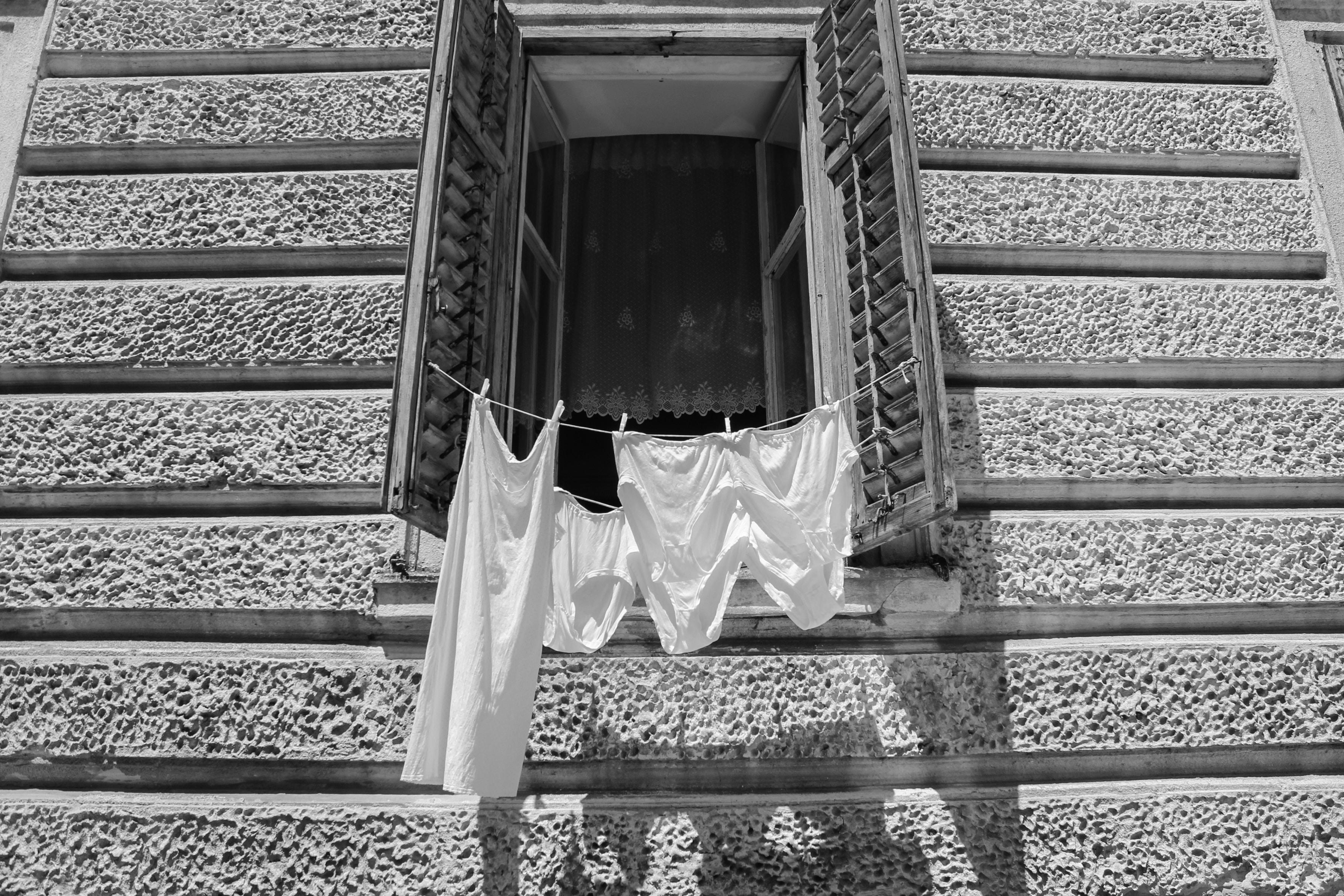 white tank top hanging on window