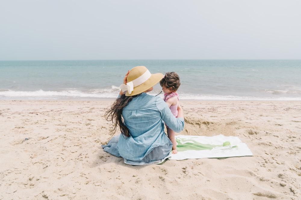 woman holding toddler on front seashore