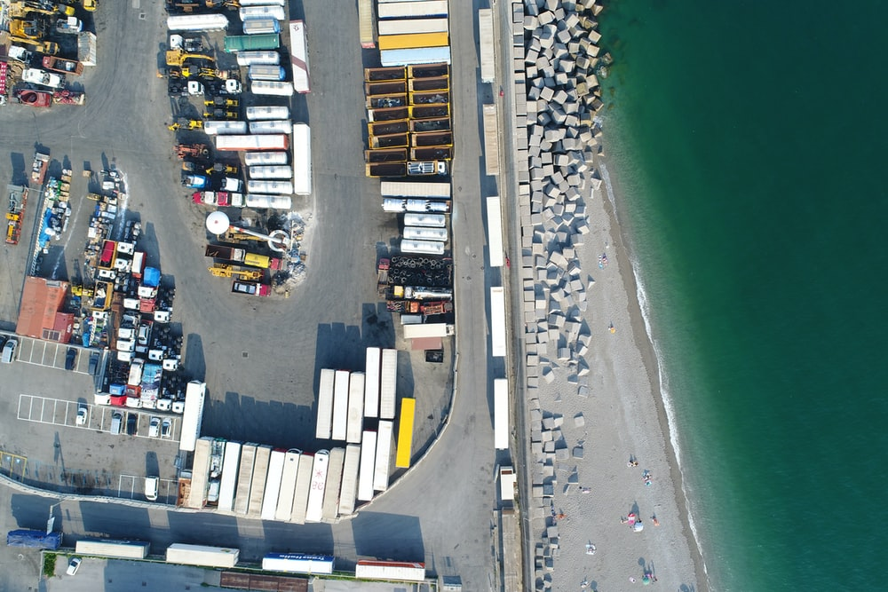 intermodal container lot near body of water during daytime