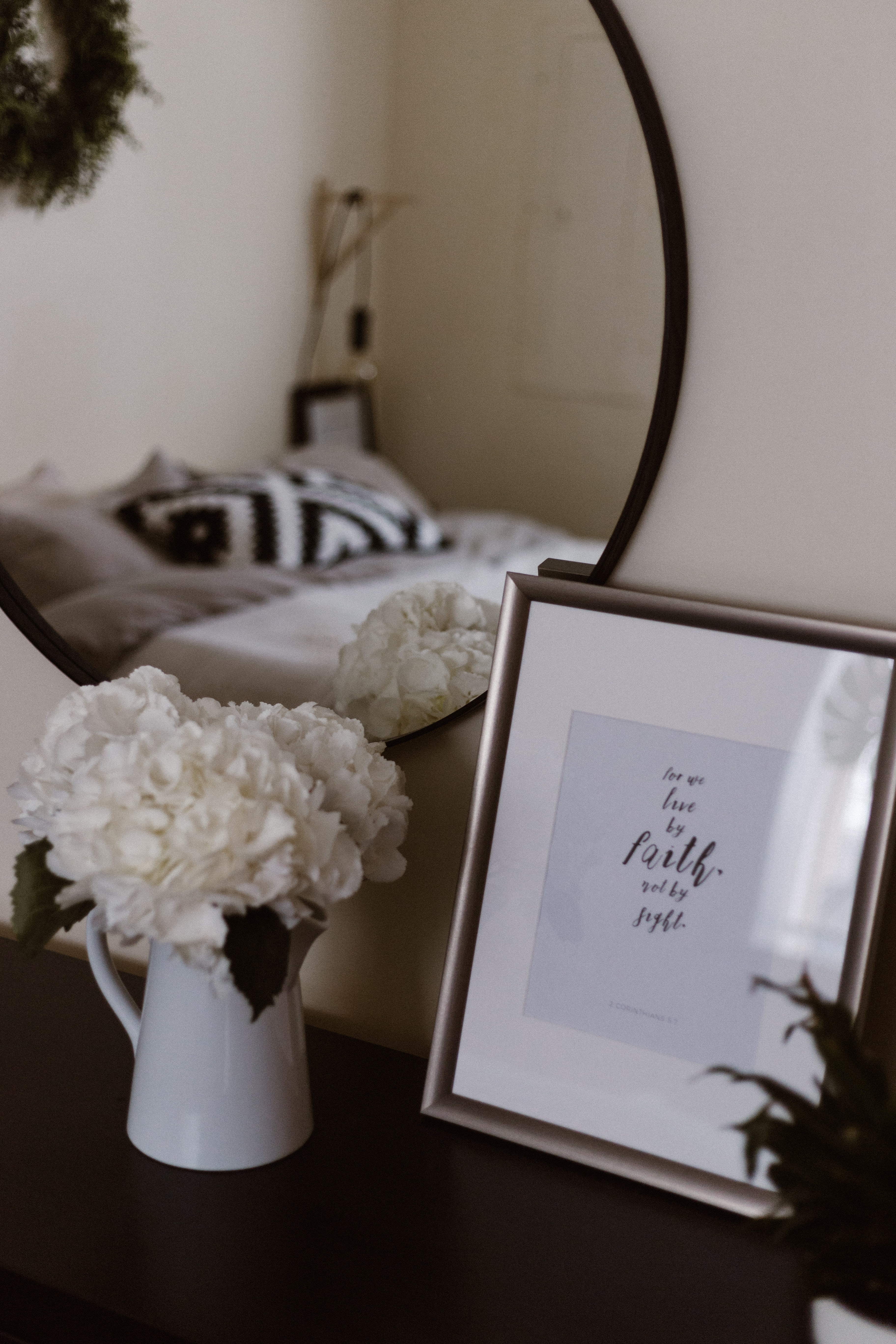 white potted flowers beside photo frame