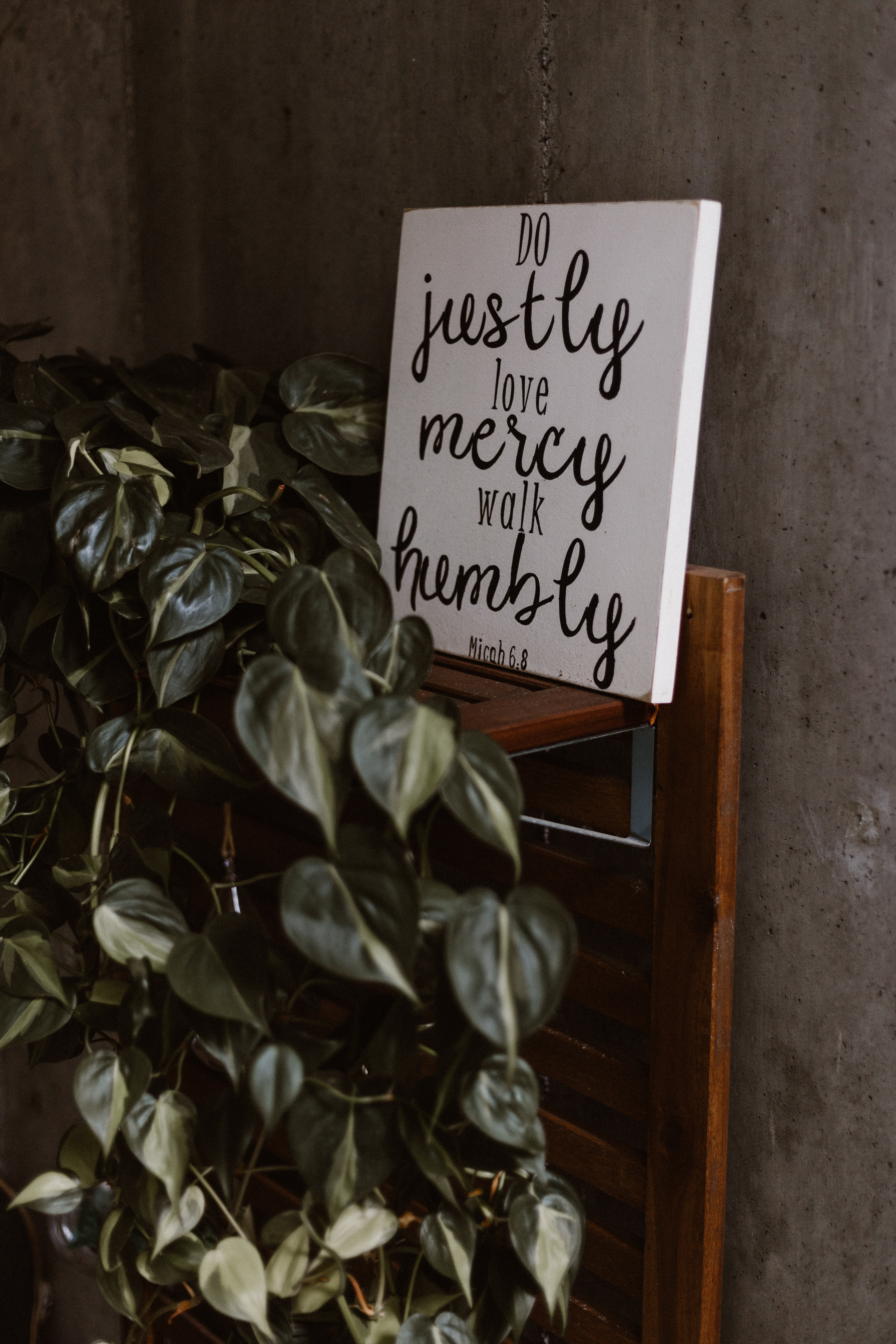 do justly love mercy walk humbly signage leaning on wall beside plants