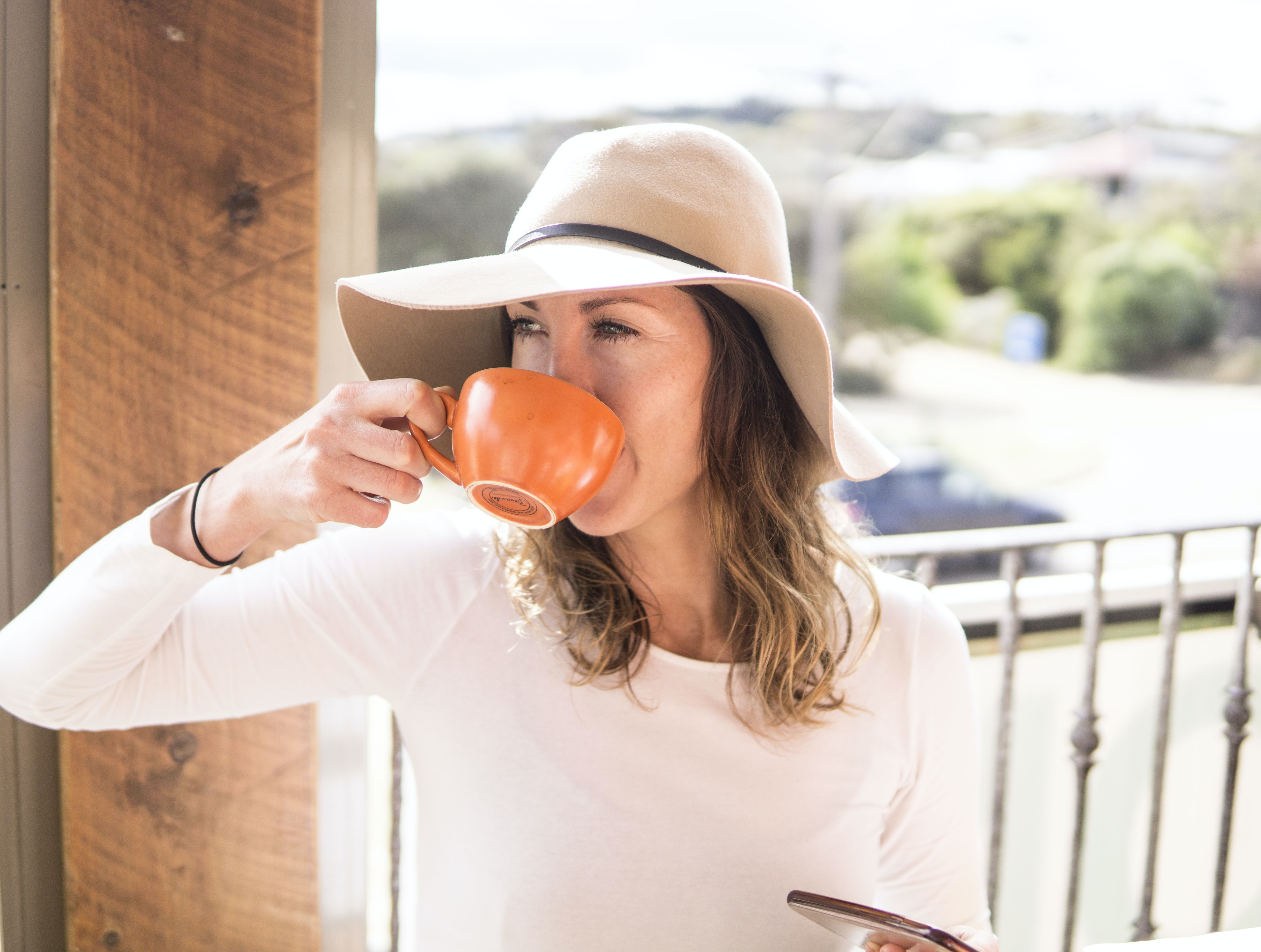woman sipping from her orange cup