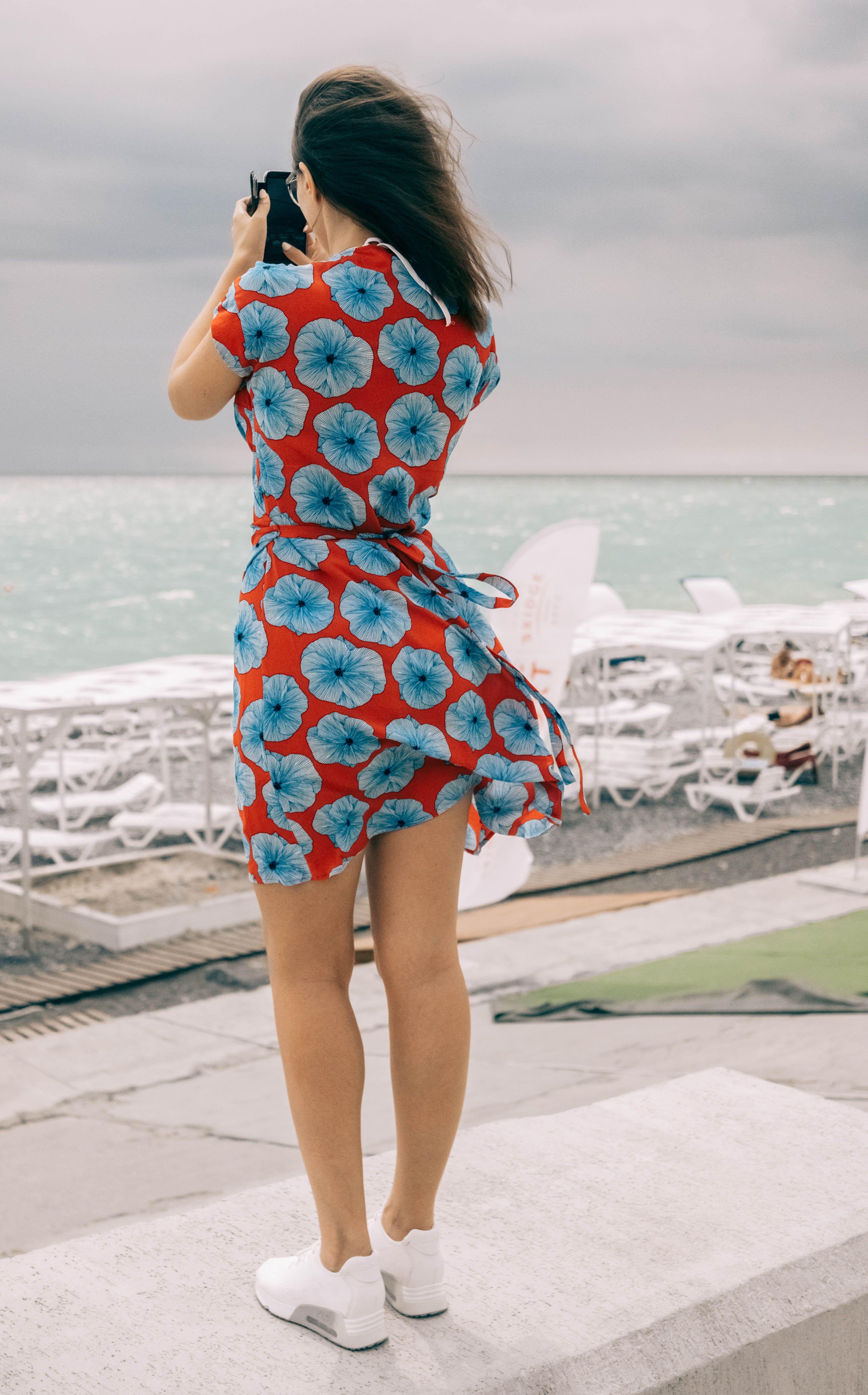 Woman Wearing Maroon And Blue Floral Dress Holding Phone At Daytime