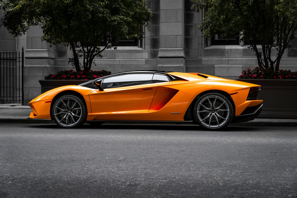 orange sports car on roadway