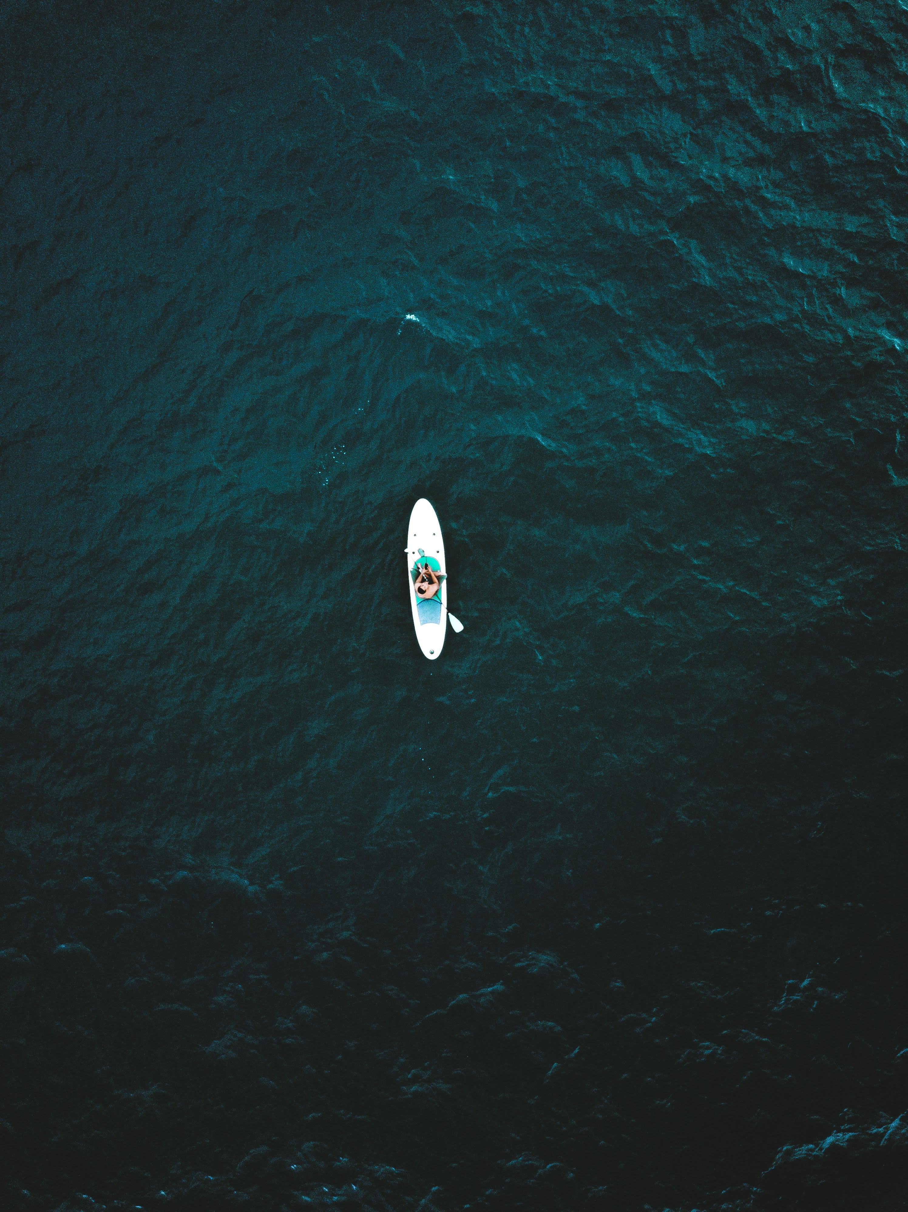 bird's-eye view of person riding in kayak on body of water