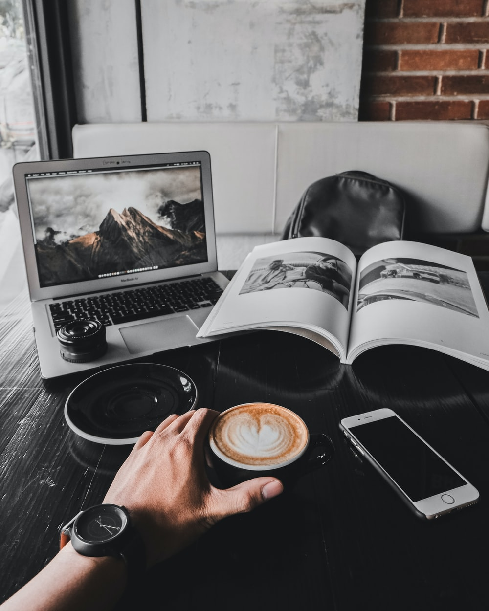 man holding cup of latte on table with MacBook Air and book
