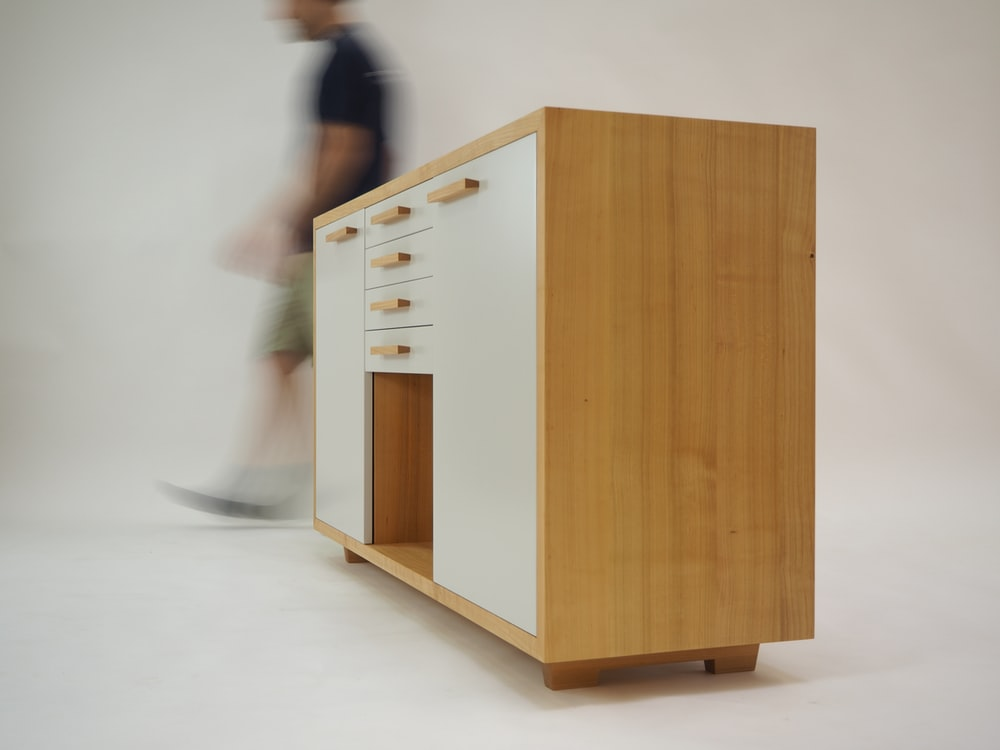 person walking beside white and brown wooden sideboard