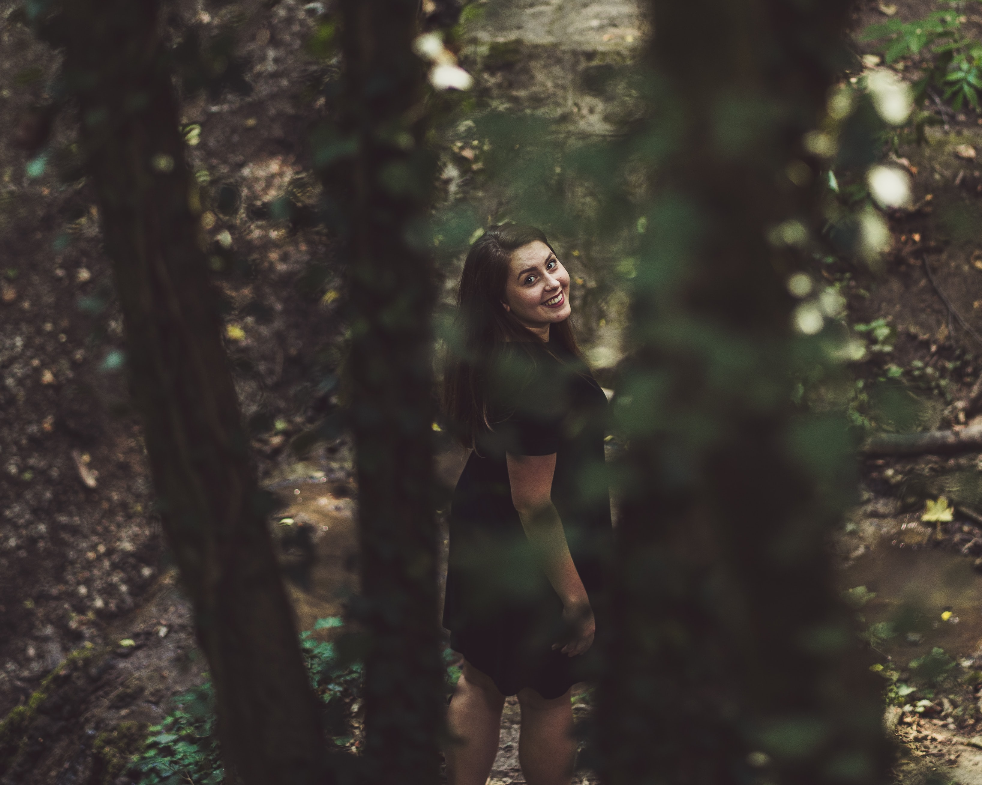 woman walking on forest while looking up