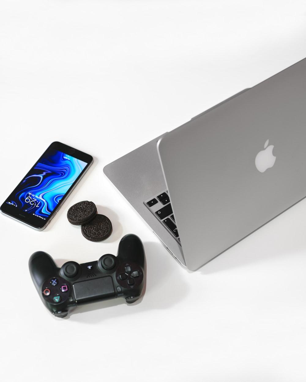 silver MacBook beside black Sony game pad