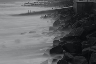 grayscale photo of waves rushed at bay long exposure teams background
