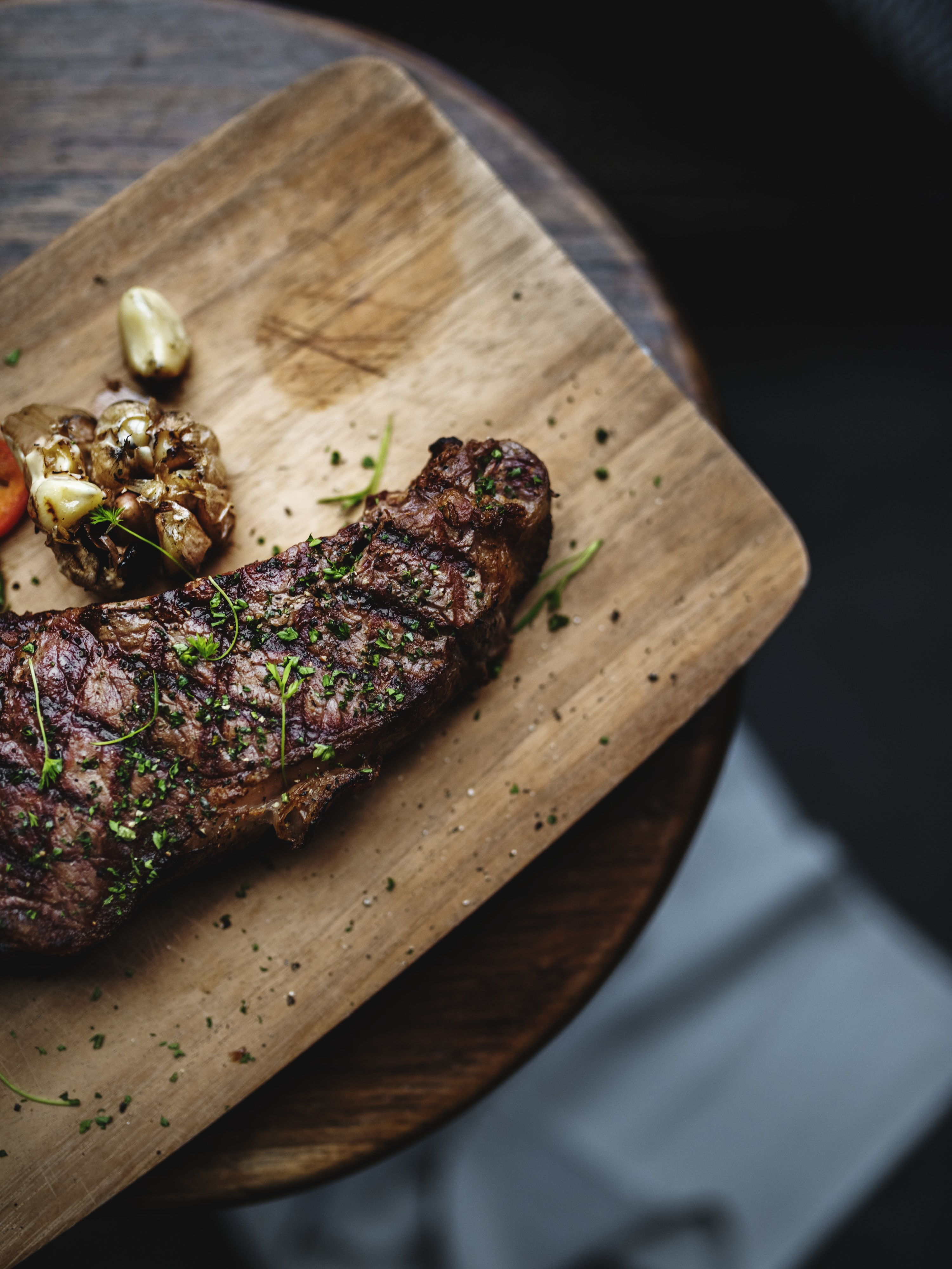 shallow focus photography of steak on wooden tray