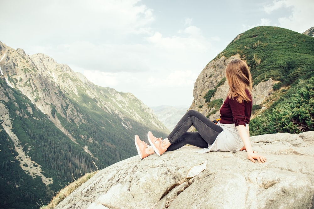 woman sitting on mountains peak