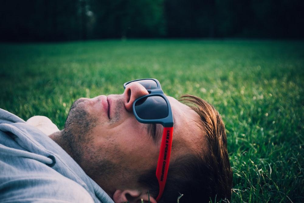 man laying on green grass field