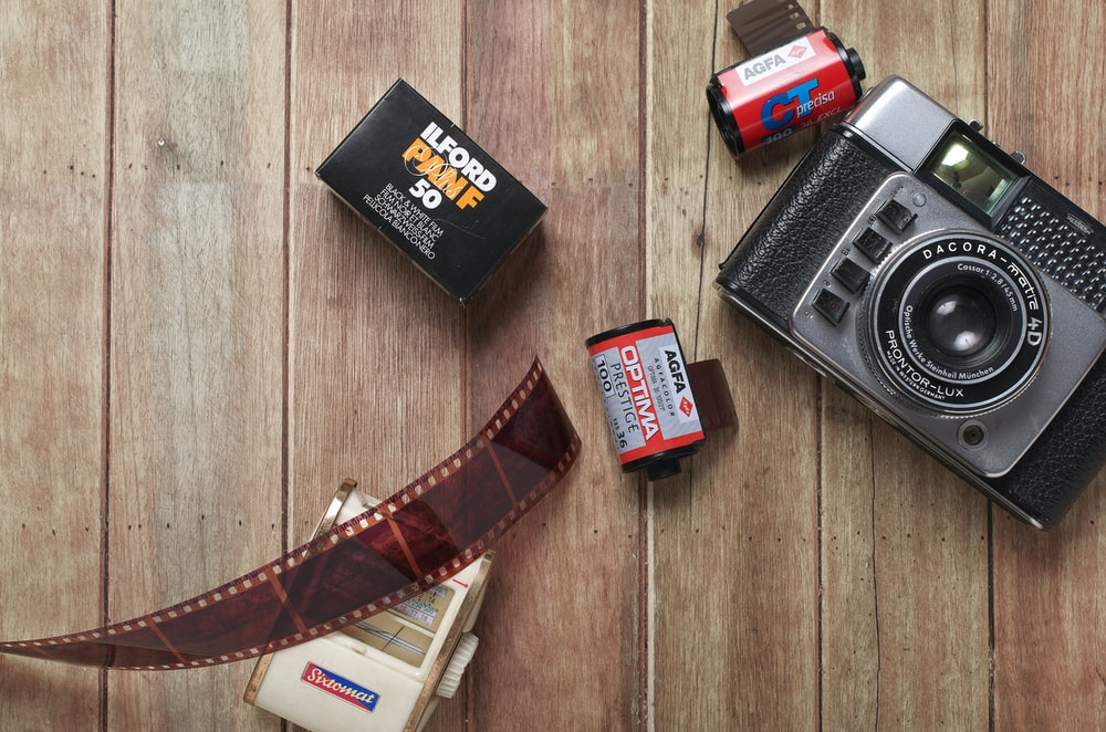 flat lay photography of film camera and films on wood parquet