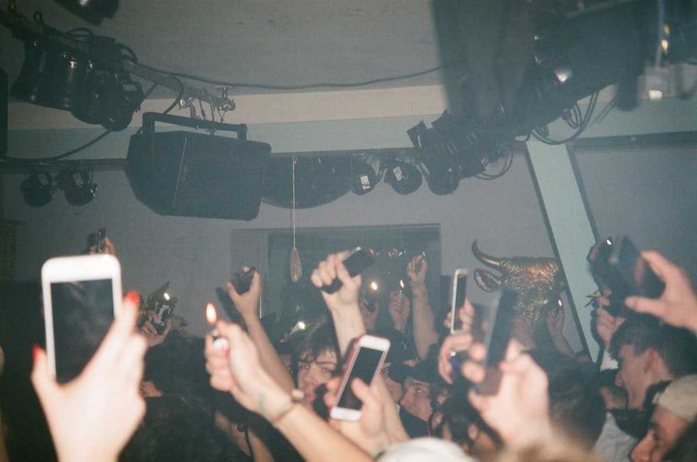 people raising their hands and holding their smartphones