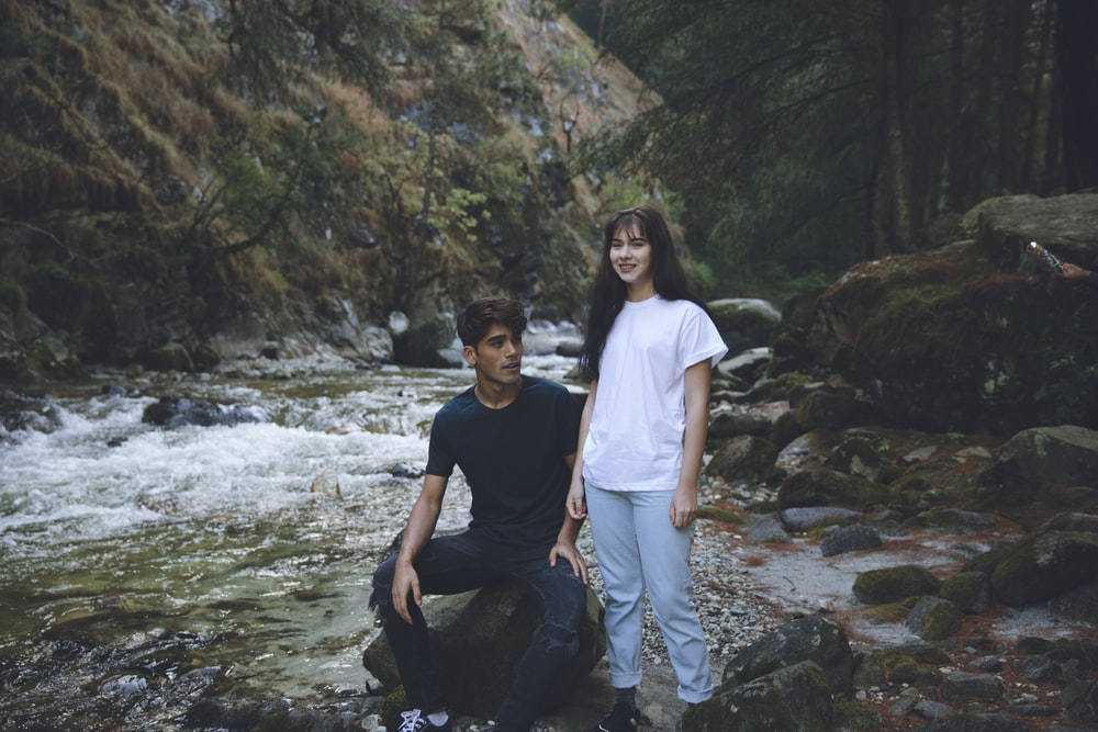man in blue shirt sitting beside woman in white shirt standing on river