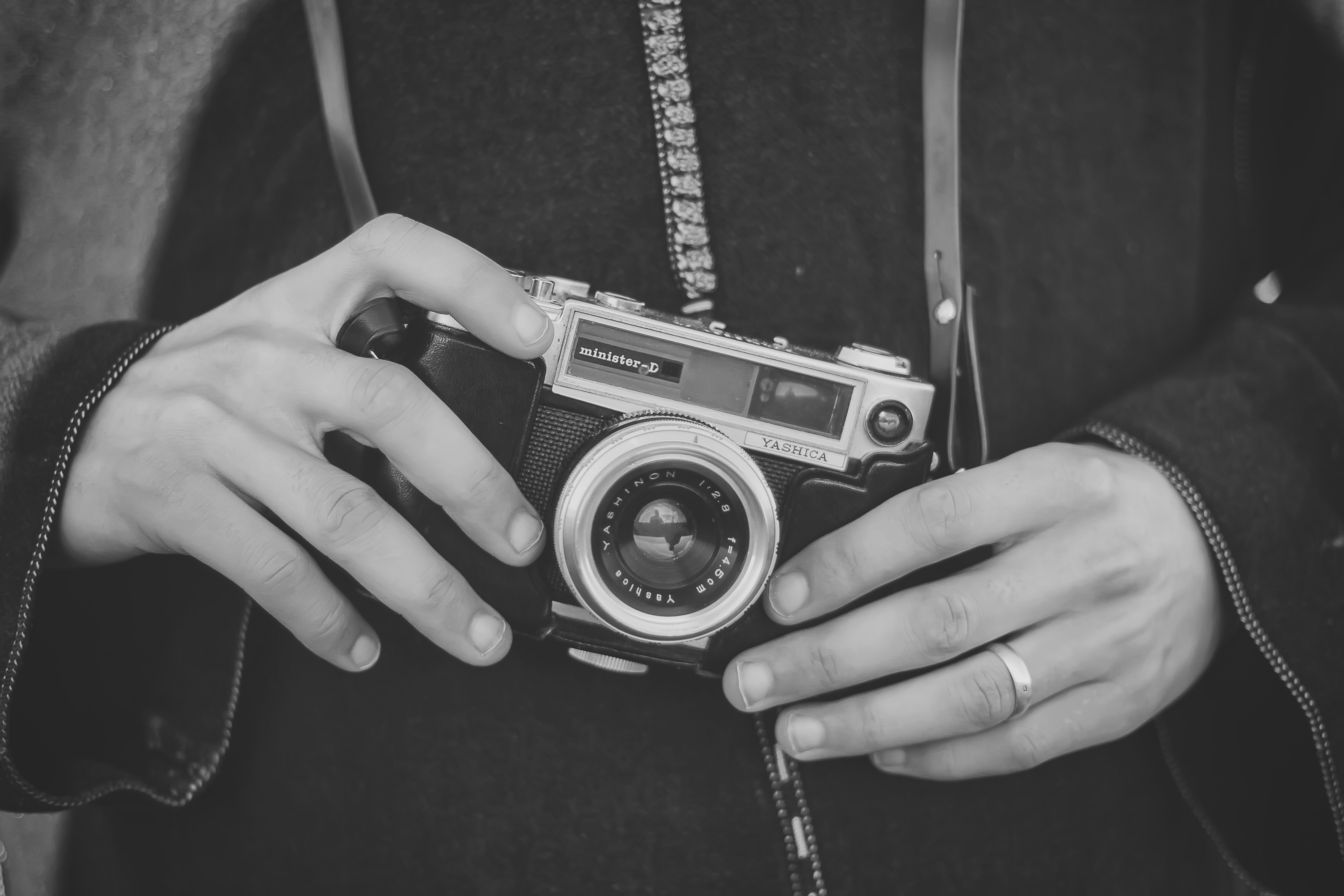 grayscale photo of person holding SLR camera