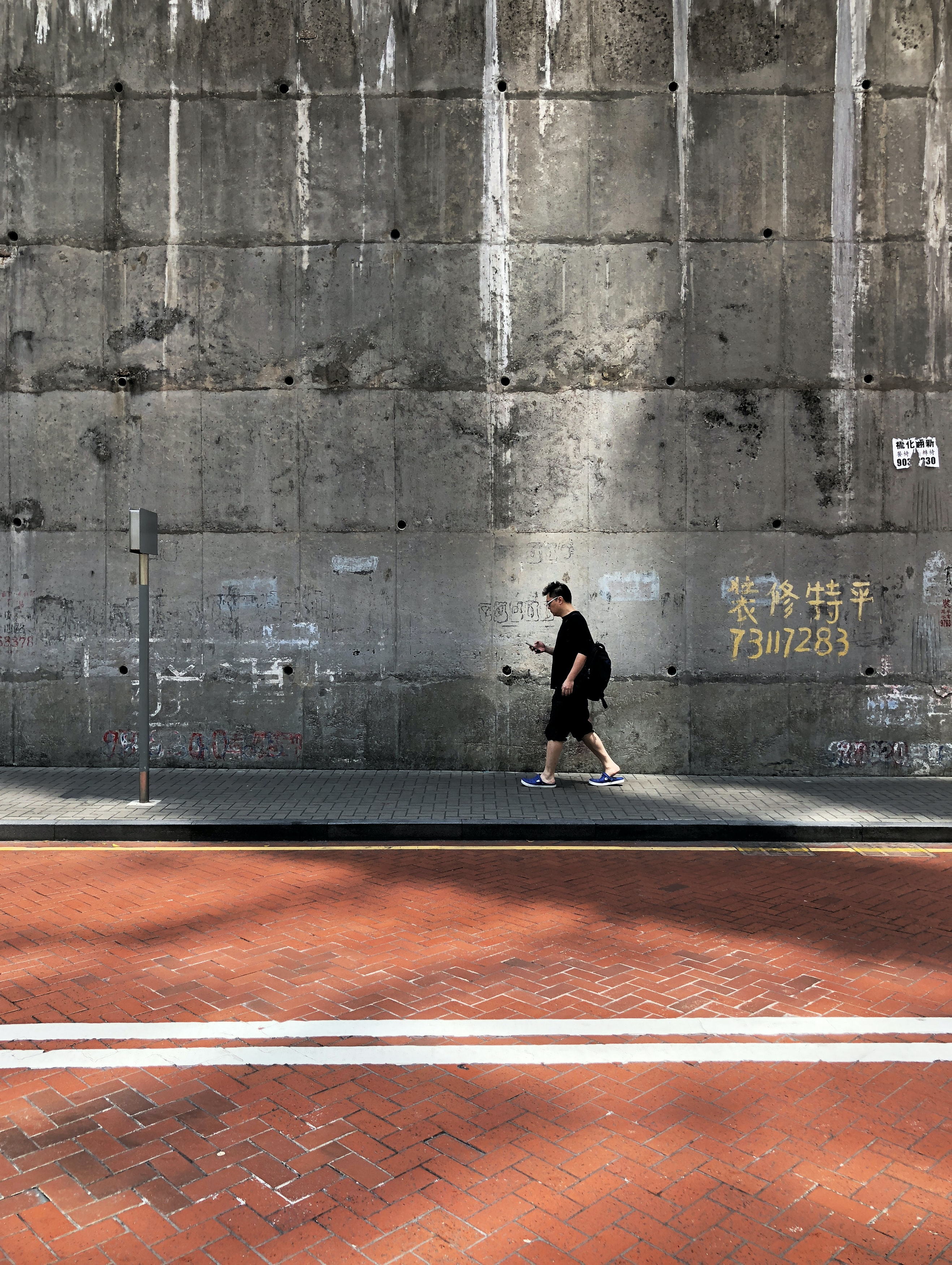 man walking beside wall and street during daytime