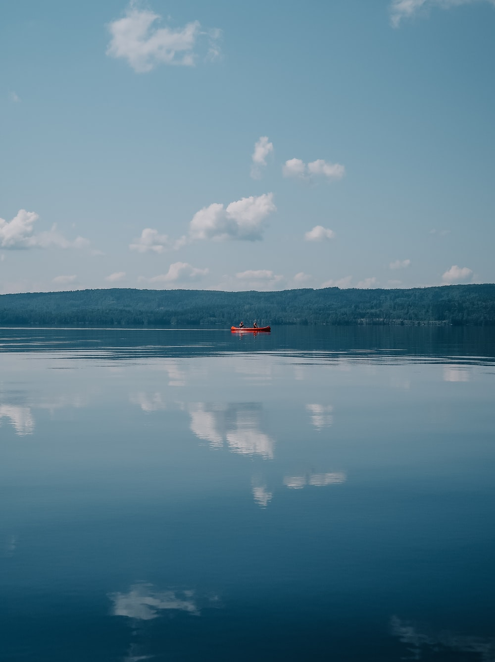 red boat on body of water under cloudy sky