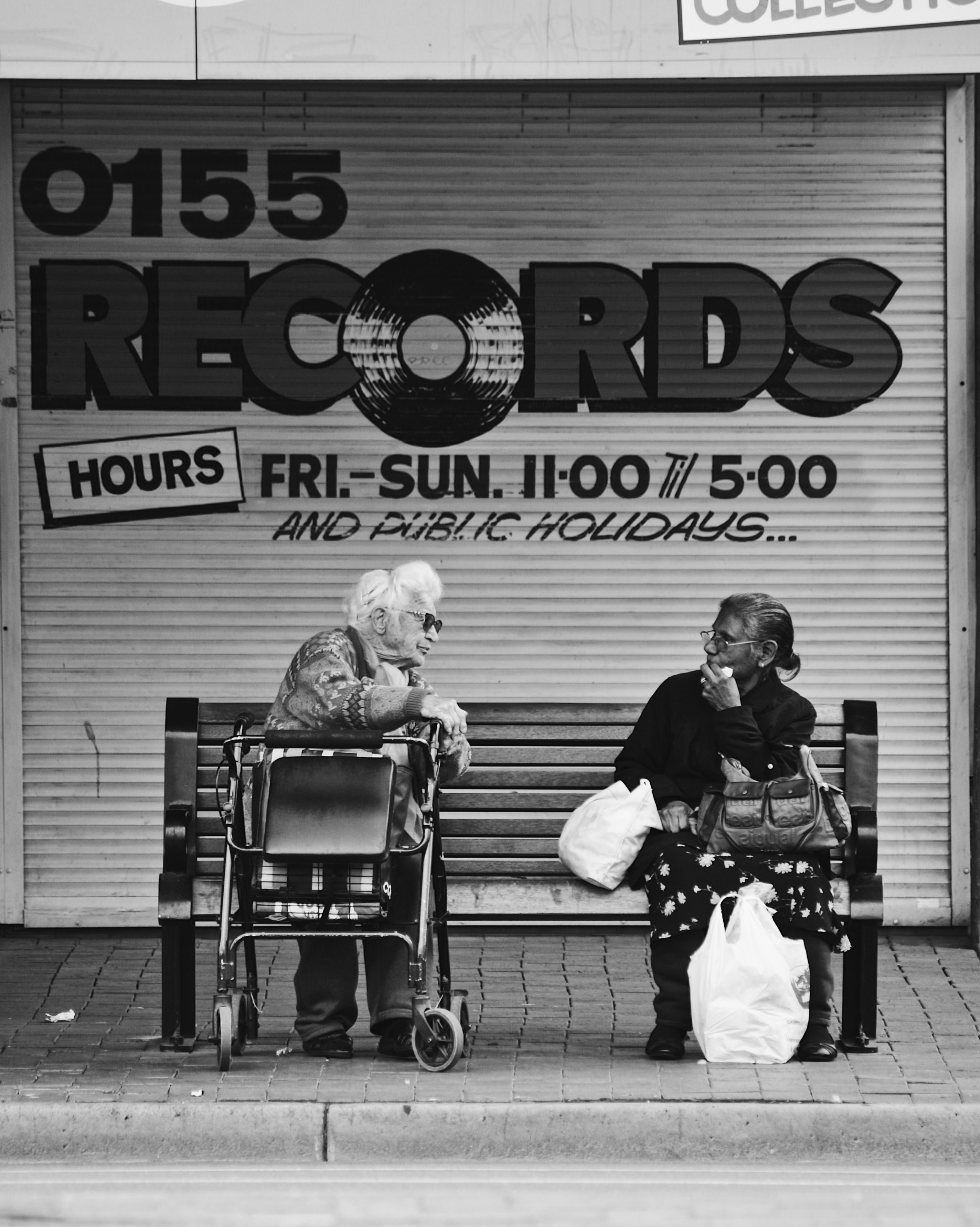 grayscale man and woman sitting on bench